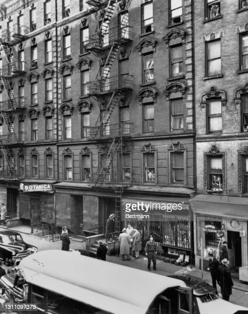 Pedestrians on the sidewalk below as residents look out from the windows of tenement buildings on the East Side of the borough of Manhattan, New York...
