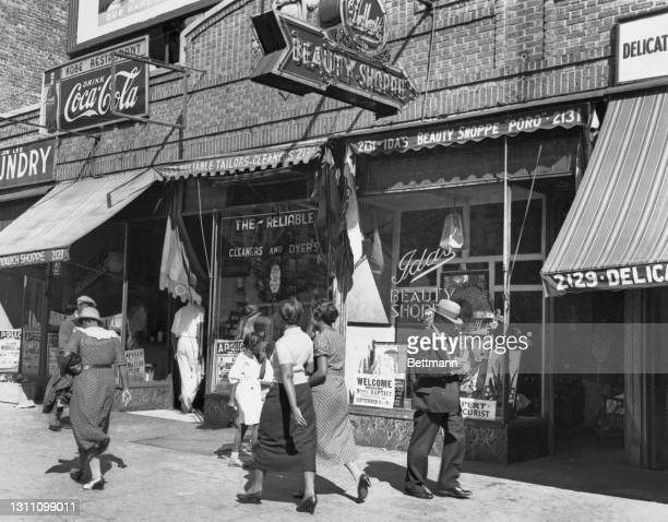 Pedestrians on the sidewalk in front of the Reliable Cleaners and Dyers, and Ida's Beauty Shoppe, on Lenox Avenue in the Harlem neighbourhood of the...
