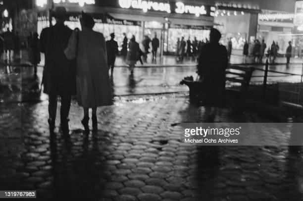 Pedestrians on wet cobbles, a Walgreen drugstore in the background, in New York City, New York, circa 1945.