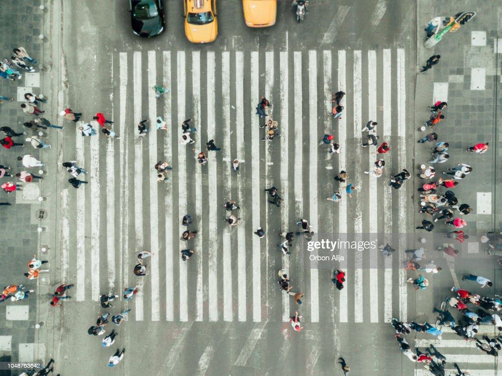 Pedestres na faixa de pedestres, e a cidade de Nova York : Foto de stock