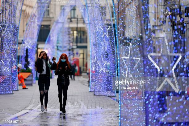 Pedestrians, one wearing a protective face covering to combat the spread of the coronavirus, walk past Christmas decorations in a street in central...