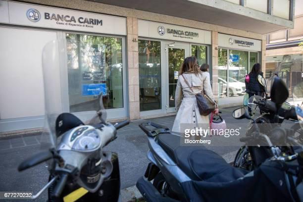 Pedestrians pass a Banca Carim Cassa di Risparmio di Rimini SpA bank branch in Rome, Italy, on Tuesday, May 2, 2017. Credit Agricole SA's Italian...