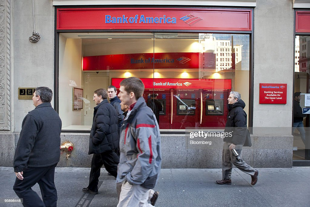 Pedestrians pass a Bank of America branch in New York, U.S., on Wednesday, Jan. 20, 2010. Bank of America Corp., the largest U.S. lender, posted a quarterly loss and its first full-year deficit in more than two decades, driven by the cost of repaying U.S. bailout money and defaults on consumer loans. Photographer: JB Reed/Bloomberg via Getty Images