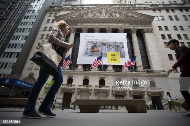 Pedestrians pass a banner displaying Amneal Pharmaceuticals Inc signage during the company's listing at the New York Stock Exchange in New York US on...