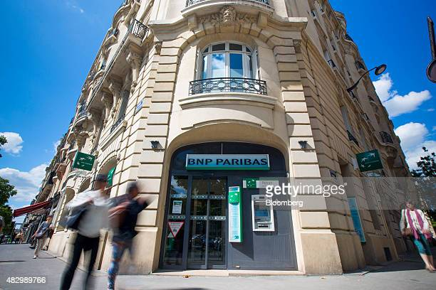 Pedestrians pass a BNP Paribas SA bank branch in Paris France on Tuesday Aug 4 2015 BNP Paribas pledged to deepen cuts at its investment bank even as...