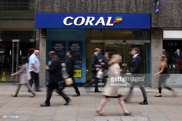 Pedestrians pass a branch of Coral bookmakers operated by Gala Coral Group Ltd in London UK on Friday July 24 2015 Ladbrokes Plc agreed to buy Coral...