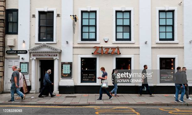 Pedestrians pass a branch of the chain Italian restaurant Zizzi in Salisbury, southern England on September 4, 2020 that was cordoned off following...