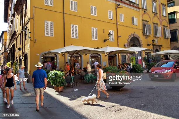 Pedestrians pass a cafe in Piazza San Michele on July 24 2015 in Lucca a city in the region of Tuscany Italy Tuscany is renowned for its landscapes...