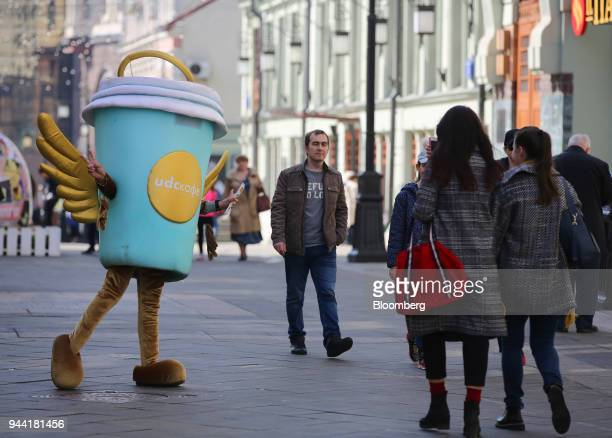Pedestrians pass a coffee promotion for the UDCUpside Down Cake Co cafe on a shopping street in Moscow Russia on Tuesday April 10 2018 Russias...