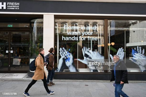 Pedestrians pass a cosmetics shop advertising free hand washing facilities in store in Liverpool northwest England on March 11 2020