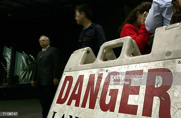 Pedestrians pass a Danger sign on a stretch of sidewalk in Times Square June 6 2006 in New York City According to the Bible's Book of Revelation 666...
