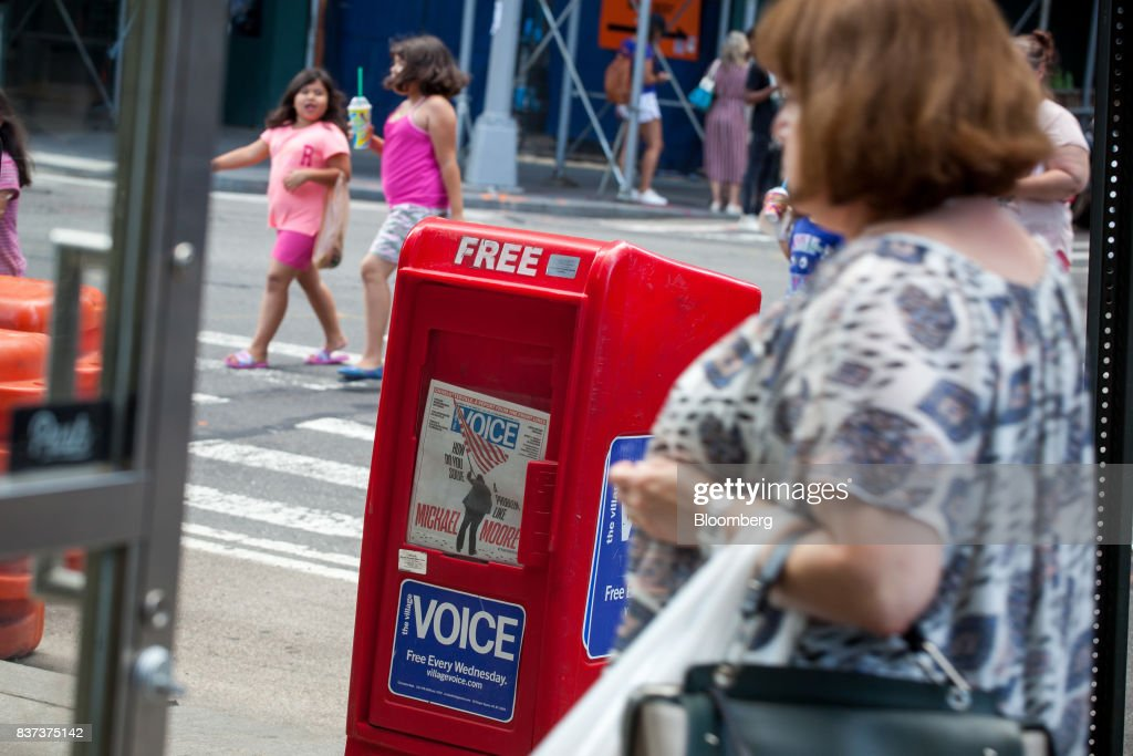 Pedestrians pass a distribution box for The Village Voice in the East Village neighborhood of New York, U.S., on Tuesday, Aug. 22, 2017. Peter Barbey, owner of The Village Voice since 2015, has decided to no longer produce a print edition of the alt-weekly publication. The company's announcement, made Tuesday afternoon, came as a surprise, a shock and a disappointment to the larger media industry on Twitter. Photographer: Michael Nagle/Bloomberg via Getty Images