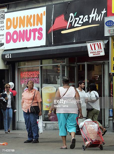 Pedestrians pass a Dunkin' Donuts and a Pizza Hut restaurant July 12, 2006 in the Brooklyn borough of New York City. In the battle to fight obesity,...