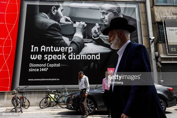 Pedestrians pass a giant advertisement for diamonds in the diamond district of Antwerp Belgium on Thursday July 20 2017 An ugly year for diamonds in...