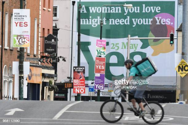 Pedestrians pass a giant poster urging a 'yes' vote in the referendum to repeal the eighth amendment of the Irish constitution a subsection that...