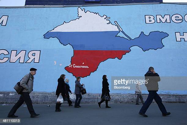 Pedestrians pass a giant wall mural showing a map of the Crimean peninsula filled with the flag of the Russian Federation in support of the Russian...