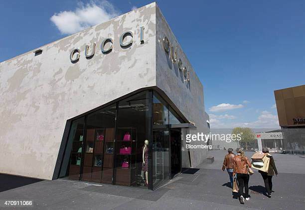 Pedestrians pass a Gucci store a luxury retail unit of Kering SA at Outlet City shopping mall operated by Holy AG in Metzingen Germany on Thursday...