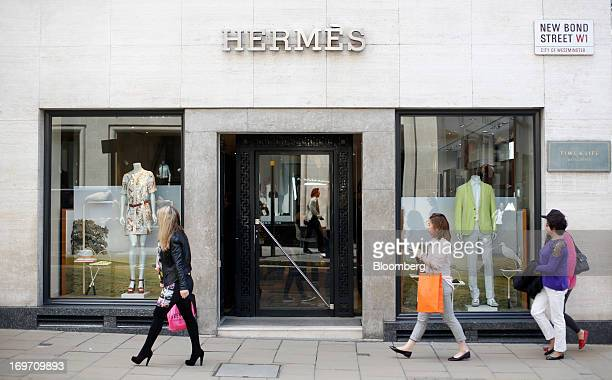 Pedestrians pass a Hermes store operated by Hermes International SCA on New Bond Street in London UK on Friday May 31 2013 LVMH Moet Hennessy Louis...