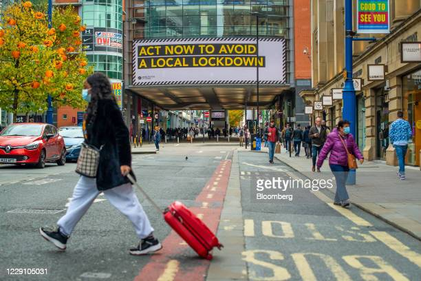 "Pedestrians pass a large advertisement on the Arndale Centre shopping mall reading ""Act now to avoid a local lockdown"" in Manchester, U.K., on..."