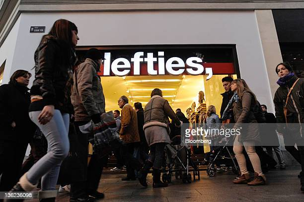 Pedestrians pass a Lefties store operated by Inditex SA in Madrid Spain on Wednesday Dec 28 2011 The Bank of Spain said available data suggest the...