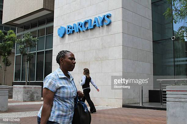 Pedestrians pass a logo outside the offices of Barclays Plc in Johannesburg South Africa on Thursday Dec 12 2013 Inflation in Africa's biggest...