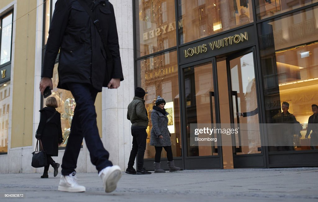 Pedestrians pass a Louis Vuitton luxury goods store, operated by LVMH Moet Hennessy Louis Vuitton SE, in Munich, Germany, on Tuesday, Jan. 9, 2018. The German economy's solid 2017 performance extended into the final three months of the year, with growth of about half a percent. Photographer: Dominik Osswald/Bloomberg via Getty Images