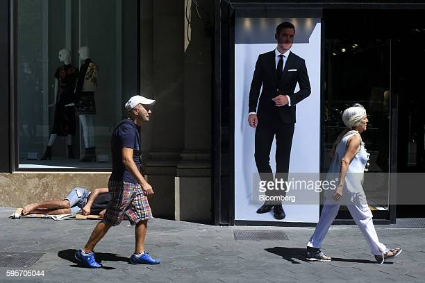 Pedestrians pass a man lying on the street outside a fashion store on Passeig de Gracia in Barcelona Spain on Thursday Aug 25 2016 'Consumption has...