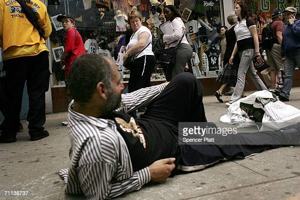 Pedestrians pass a man reclining on the street June 6 2006 in New York City According to the Bible's Book of Revelation 666 is the mark of the beast...