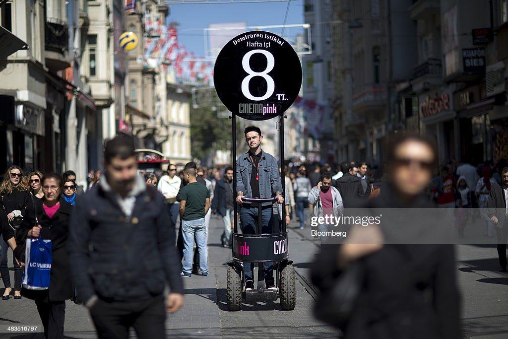 Pedestrians pass a man standing aboard a mobile platform advertising a price promotion for 'Cinema Pink' on Istiklal street in Istanbul, Turkey, on Wednesday, April 9, 2014. Turkish central bank Governor Erdem Basci indicated to analysts in London on April 3 that he planned to keep monetary policy tight to control inflation. Photographer: Kerim Okten/Bloomberg via Getty Images