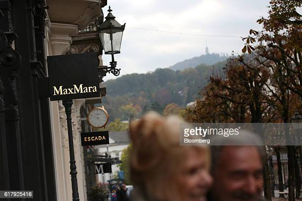 Pedestrians pass a Max Mara Fashion Group Srl clothing fashion store at dusk in BadenBaden Germany on Monday Oct 24 2016 The world's luxurygoods...