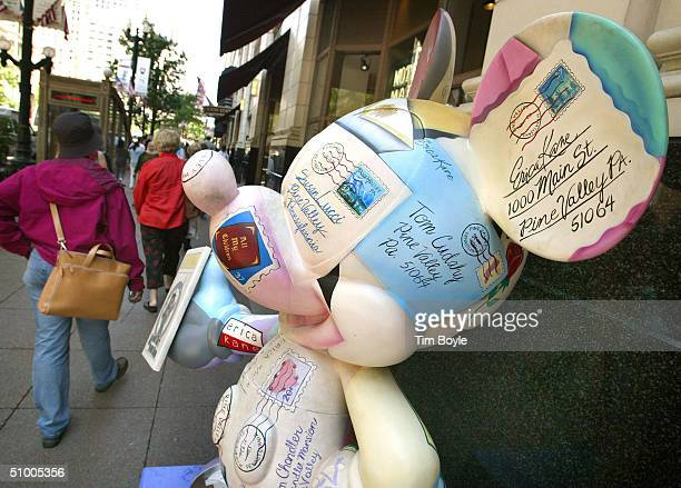 Pedestrians pass a Mickey Mouse statue titled 'All The World's His Stage' designed by Susan Lucci on State Street June 28 2004 in Chicago Illinois...