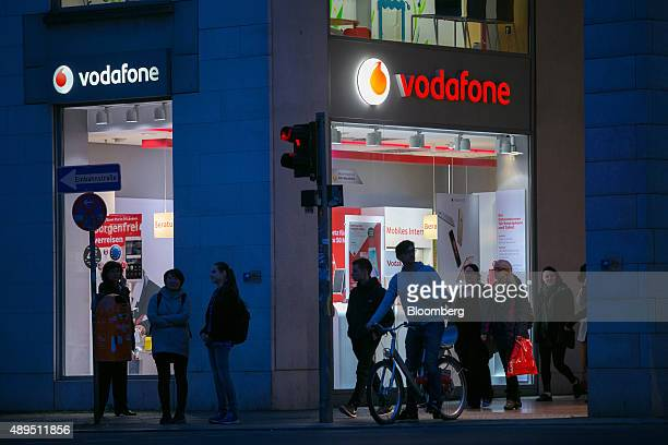 Pedestrians pass a mobile phone store operated by Vodafone Group Plc at night in Berlin Germany on Monday Sept 21 2015 Liberty Global Plc is still...