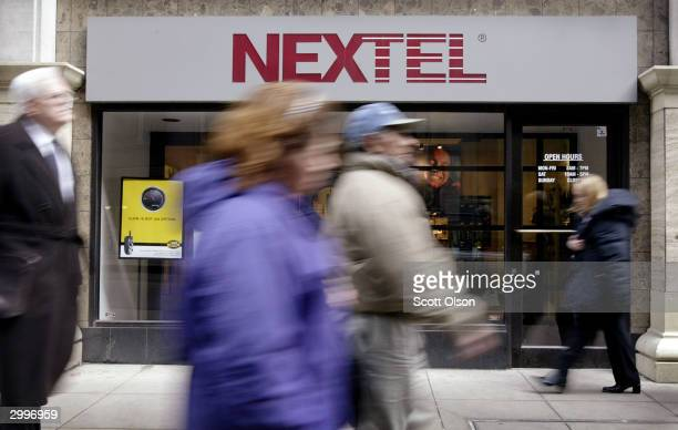 Pedestrians pass a Nextel store February 19 2004 in downtown Chicago Illinois Nextel's fourth quarter earnings dropped sharply from the previous year...