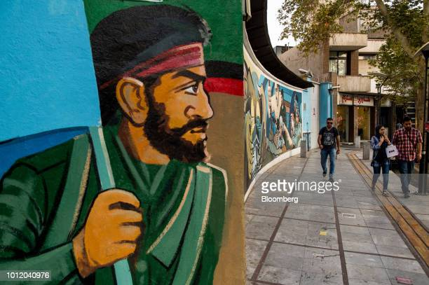 Pedestrians pass a political war mural on a wall in Tehran Iran on Sunday Aug 5 2018 Irans central bank acting on the eve of US sanctions scrapped...