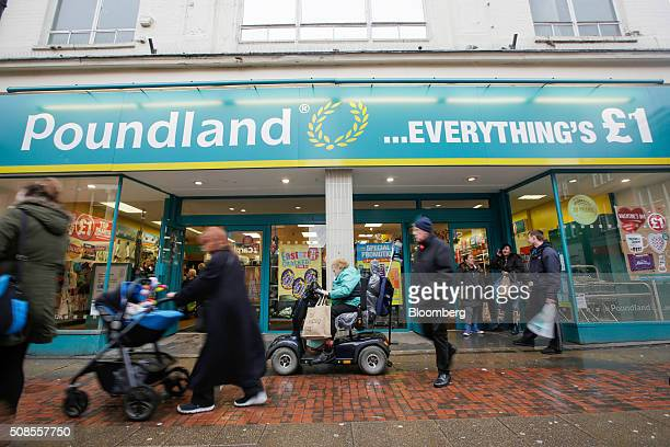 Pedestrians pass a Poundland Group Plc store in Leigh UK on Thursday Feb 4 2016 UK like for like sales at midmarket retailers rose 14 percent in...
