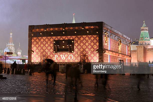 Pedestrians pass a promotional exhibit for Louis Vuitton a large wooden chest adorned in the trademark pattern and logo of luxury manufacturer LVMH...