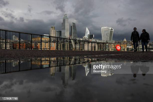 Pedestrians pass a puddle reflecting skyscrapers in the skyline of the City of London, U.K., on Thursday, Oct. 15, 2020. London is on course for an...