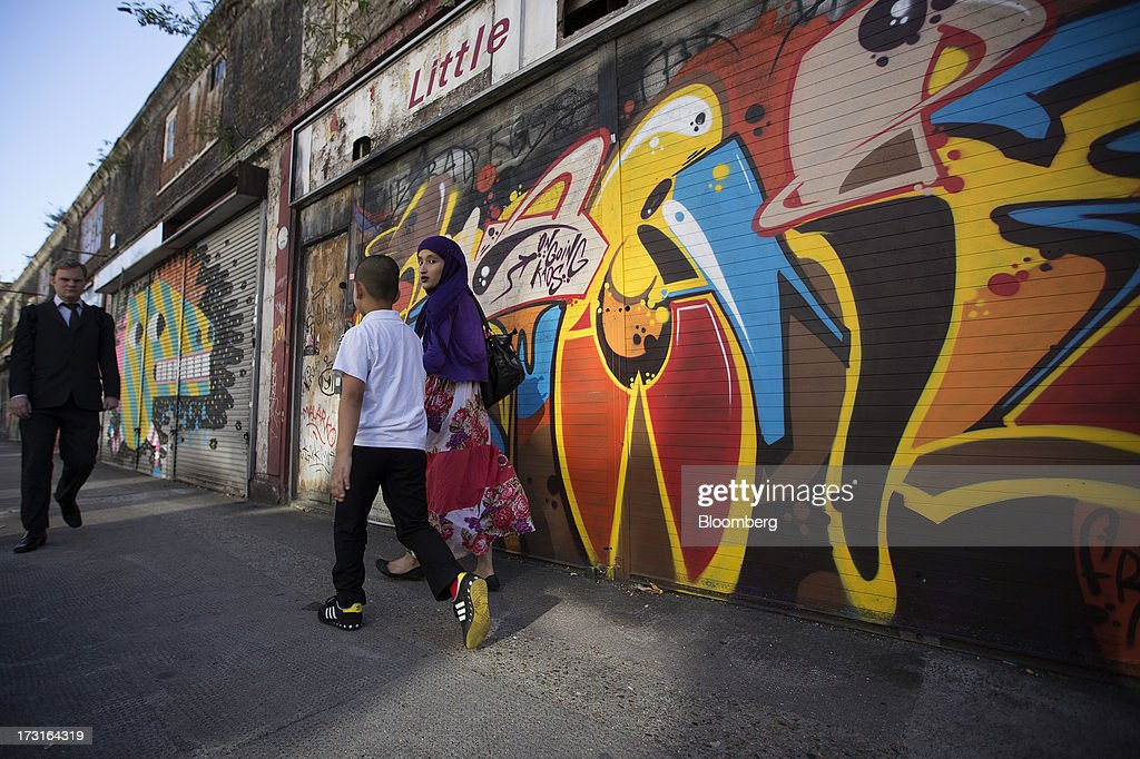Pedestrians pass a row of graffiti covered shutters outside closed stores in London, U.K., on Monday, July 8, 2013. Britain's economy could be in line for a period of 'strong catch-up growth' once it gets through the current weakness, according to Capital Economics Ltd. Photographer: Simon Dawson/Bloomberg via Getty Images