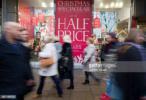 Pedestrians pass a sale sign on Oxford Street one of the main shopping streets in central London on December 13 2015 less than two weeks before...