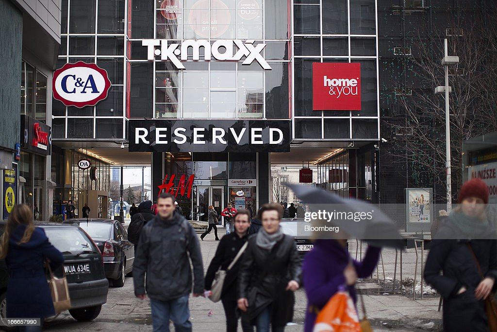 Pedestrians pass a shopping mall advertising TK Maxx, C&A and Home&You brands in Warsaw, Poland, on Thursday, April 11, 2013. Poland's central bank kept interest rates unchanged at a record-low 3.25 percent yesterday. Photographer: Bartek Sadowski/Bloomerg