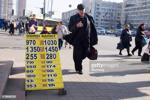 Pedestrians pass a sign advertising foreign exchange rates including rubles euros and dollars outside a currency store in Kiev Ukraine on Friday...