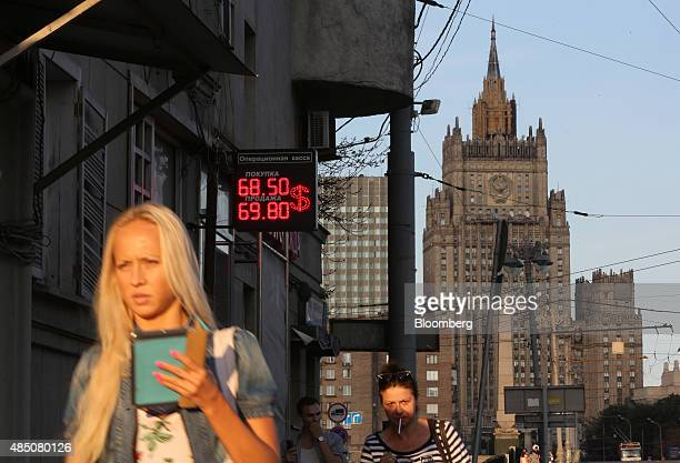 Pedestrians pass a sign advertising US dollar exchange rates outside a currency exchange bureau near the headquarters of the Russian Ministry of...