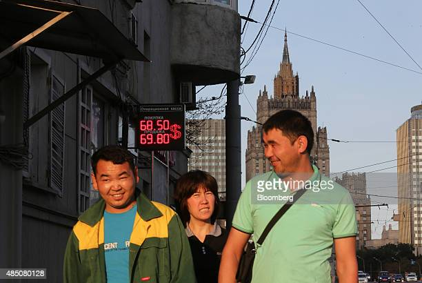 Pedestrians pass a sign advertising US dollar exchange rates outside a currency exchange bureau in Moscow Russia on Sunday Aug 23 2015 The Russian...