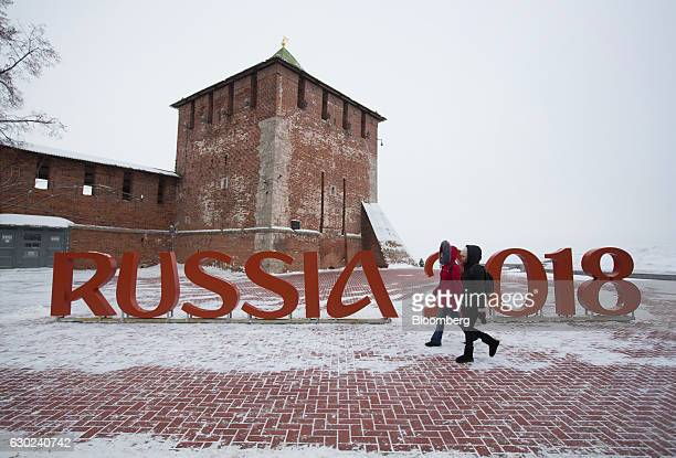 Pedestrians pass a sign for Russia 2018 FIFA World Cup at the kremlin fort in Nizhny Novgorod Russia on Saturday Dec 17 2016 Nizhny Novgorod is one...