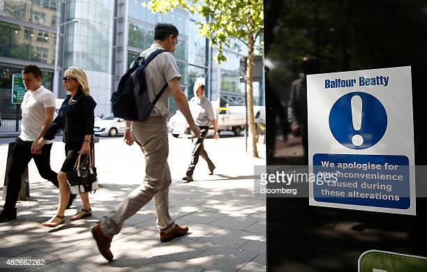 Pedestrians pass a sign on hoardings surrounding a Balfour Beatty Plc construction site in the Euston district of London UK on Friday July 25 2014...
