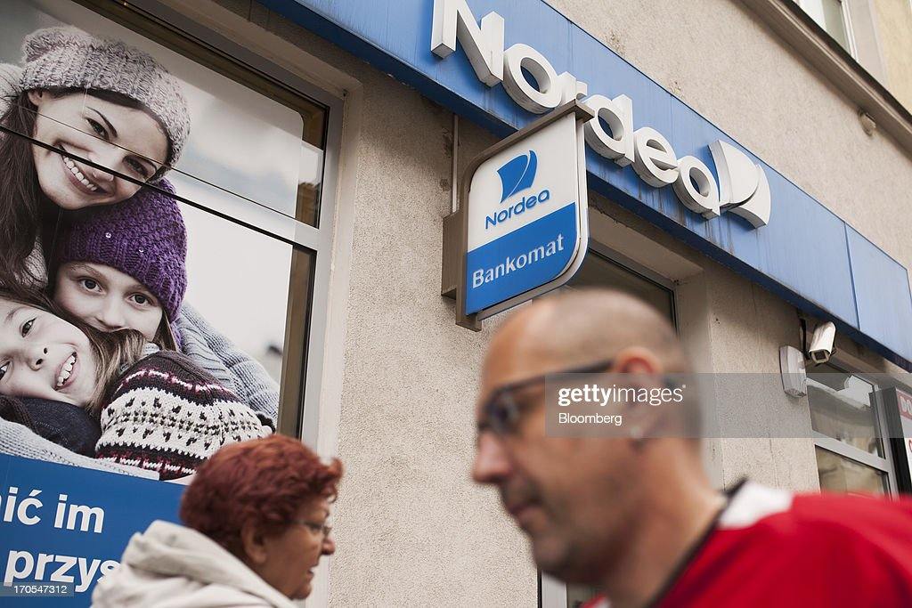 Pedestrians pass a sign outside a Nordea Bank Polska SA bank branch in Wroclaw, Poland, on Friday, June 14, 2013. PKO Bank Polski SA, Poland's biggest lender, surged to a five-month high after signing an agreement to buy Nordea Bank AB's Polish assets to increase its dominance on the European Union's largest eastern market. Photographer: Bartek Sadowski/Bloomberg via Getty Images