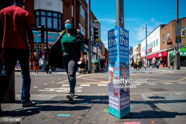 Pedestrians pass a sign reading Stop the Spread referring to the spread of COVID19 by maintaining the British government's current social distancing...