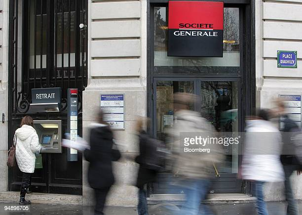 Pedestrians pass a Societe Generale bank branch as a customer withdraws cash from an ATM in Paris France on Wednesday Feb 20 2008 Societe Generale...