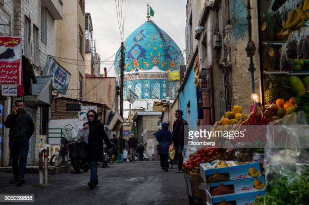 Pedestrians pass a store selling groceries near a mosque in Tehran Iran on Sunday Jan 7 2018 A wave of bad loans from unregulated lenders has rocked...