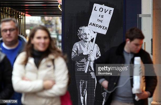 Pedestrians pass a 'street art' depiction of the scientist Albert Einstein holding a banner reading 'Love is the answer' at a construction site on...